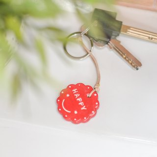 "The red smiley key chain(key ring) with the word "" HAPPY ""."
