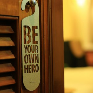 "[EyeDesign see design] a word door hanging ""BE YOUR OWN HERO"" D20"