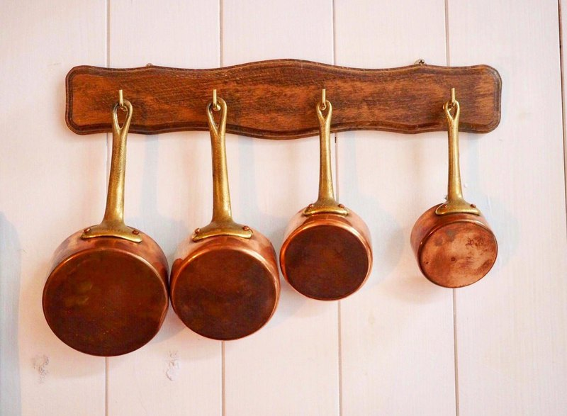 British Collection 1950s red copper sauce pot four-piece set with wall-mounted wooden rack