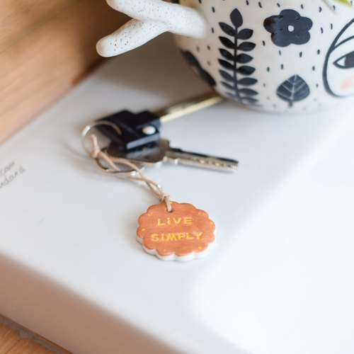 "The key chain(key ring) with the word "" Live Simply ""."