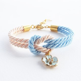 Light blue and ivory cream knot rope bracelet with blue sakura charm
